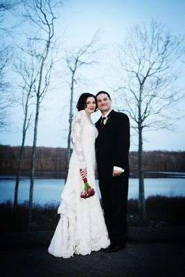 Stylish Bride and Groom Pose Outside in front of Lake