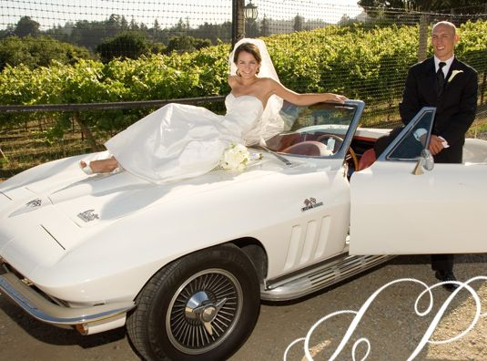 Bride and Groom pose on their vintage, white wedding car