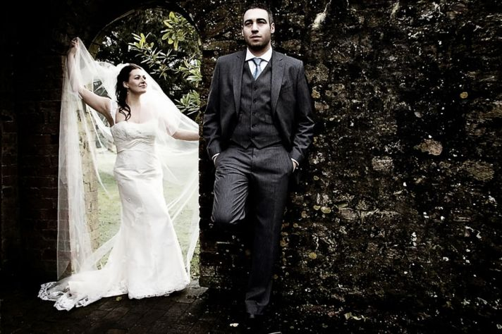 Bride in white wedding dress holds veil, together with groom outside in forest