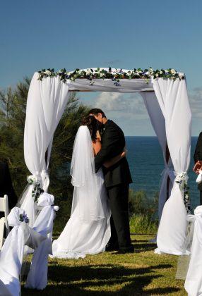 backyard wedding bride groom white canopy garlands