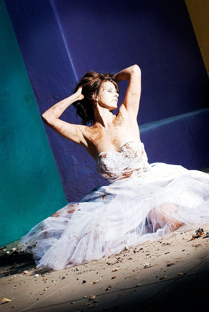 Trash the dress- bride in white strapless wedding dress, dirt, blue and teal background