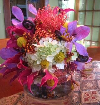 Low table centerpiece with bright fuchsia, white, yellow, and lilac flowers