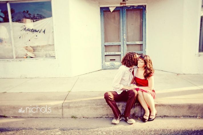 Bride and groom sit outside on curb in front of store, groom kisses bride