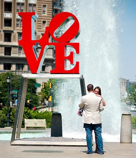Newly engaged couple hug outside, in front of fountain and red LOVE sculpture