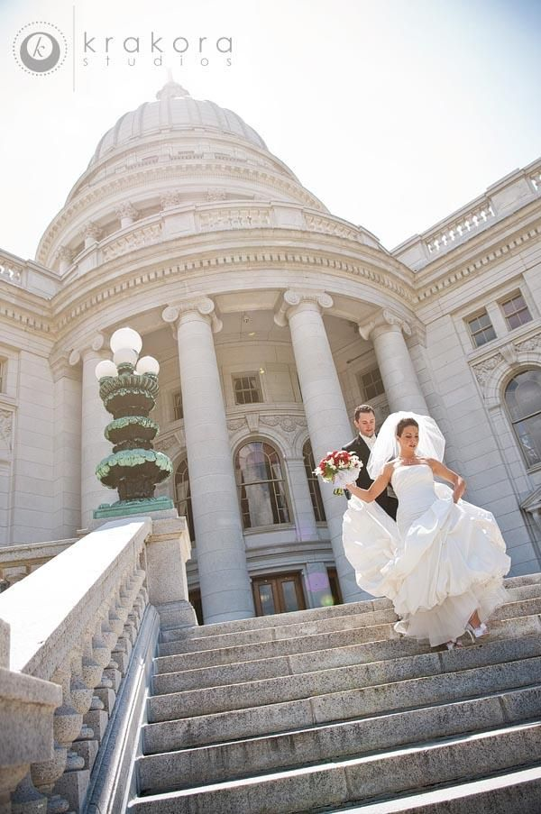 Bride and groom walk down steps of capital building, bride holds red and white bouquet