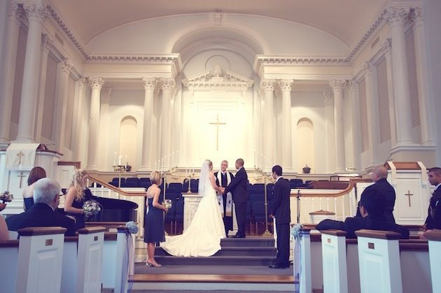 Bride in long white dress and groom in black tux stand at the altar.