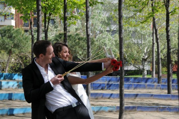 Groom in open neck suit and bride holding a red bouquet shoot a slingshot together