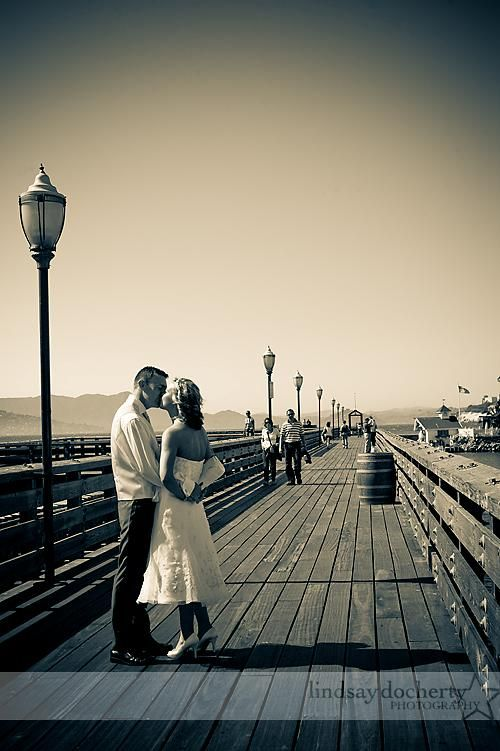 Stunning vintage-inspired wedding photo of bride and groom kissing on pier