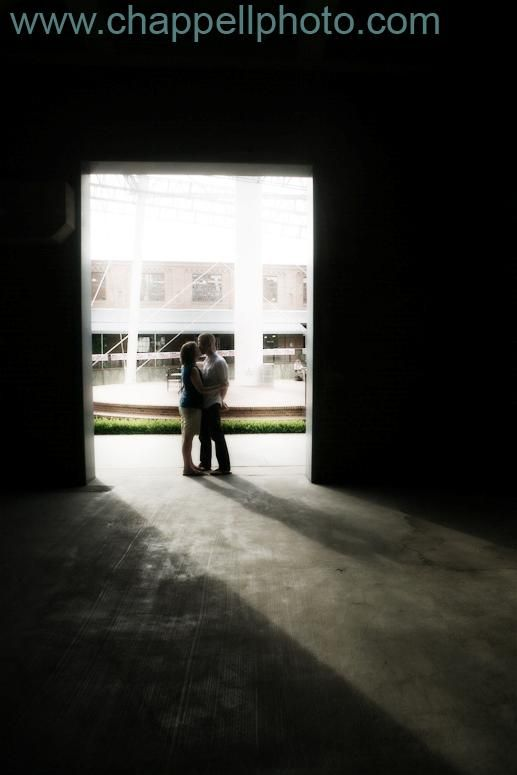 Bride and groom kiss in bright lighted doorway, surrounding area is dark