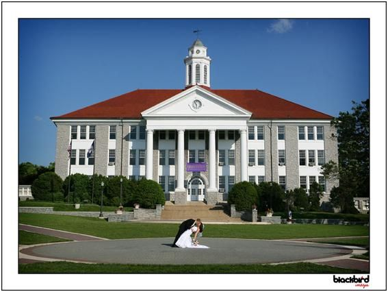 Bride and groom kiss on JMU grounds in front of university building