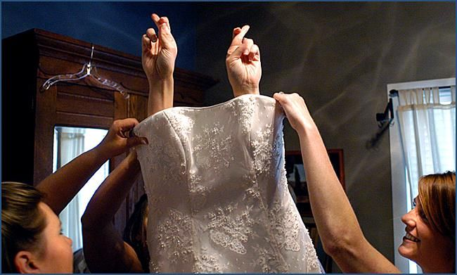 Bridesmaids hold wedding dress as bride slips in, fingers crossed