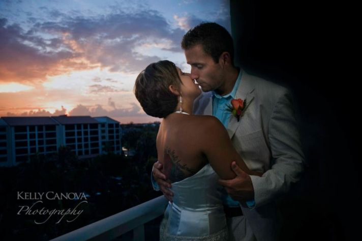 Sunset and the hotel balcony are the perfect backdrops for this short-haired bride's kiss with her g