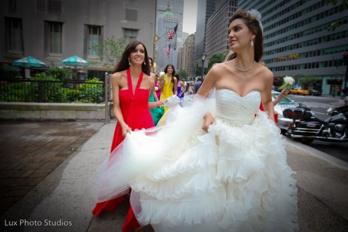 A strapless white dress is always appropriate on a bride. This bride's low cut bodice and full skirt