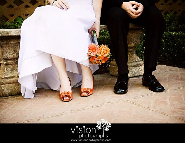 Bride in white wedding dress with bright orange peep toe heels and bouquet, groom in formal tux shoe