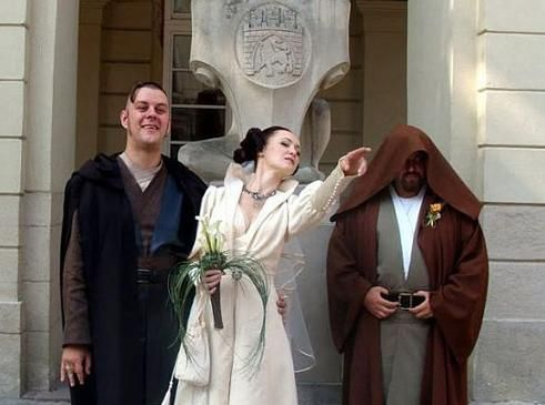 A bride, groom, and officiant are dressed in star wars wedding outfits.