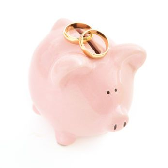 This pink piggy bank with gold wedding rings helps remind us that weddings and money are related.