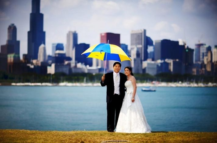 Bride and groom pose with umbrella in front of Chicago's skyline
