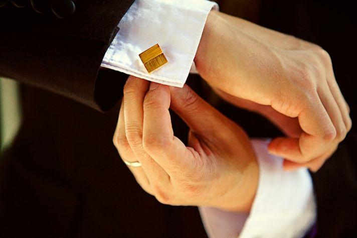 Wedding detail shot: Groom's white french cuffs, black tuxedo, gold cufflinks