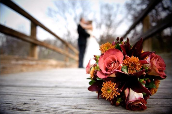 Stunning fall bridal bouquet (with pink roses and orange and maroon flowers) sits on wood dock, brid