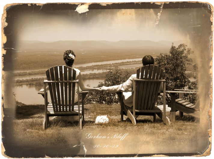 This sepia toned photograph shows a bride and groom planning their life together in outdoor chairs.