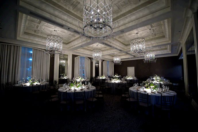 Stunning Wedding Reception Room With Sparkling Chandeliers And Round Black Receptions