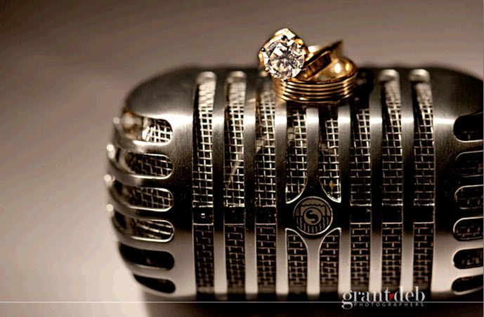 Gold wedding bands and diamond engagement ring sits atop vintage microphone