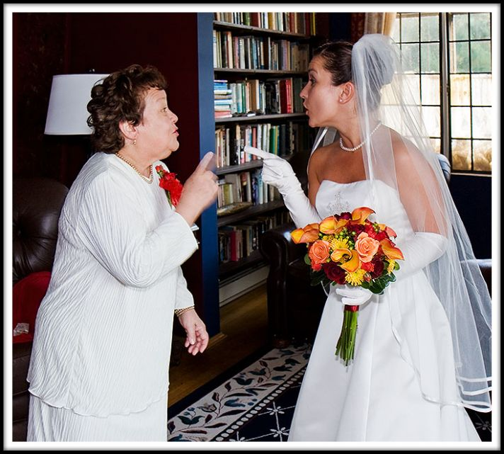 This bride in her beautiful strapless wedding dress and veil with an orange, yellow and red bouquet