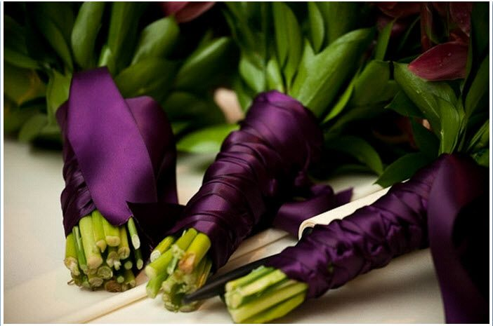 Bridesmaids beautiful floral bouquets wrapped with deep eggplant purple