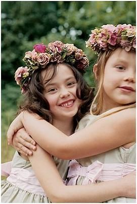 These two flower girls are wearing beautiful wreaths in their hair.