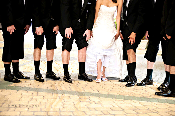 Fun wedding photo groom and groomsmen lift tux pants bride lifts white