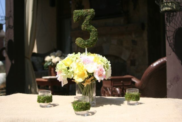 This moss table number is set in white and pink roses.