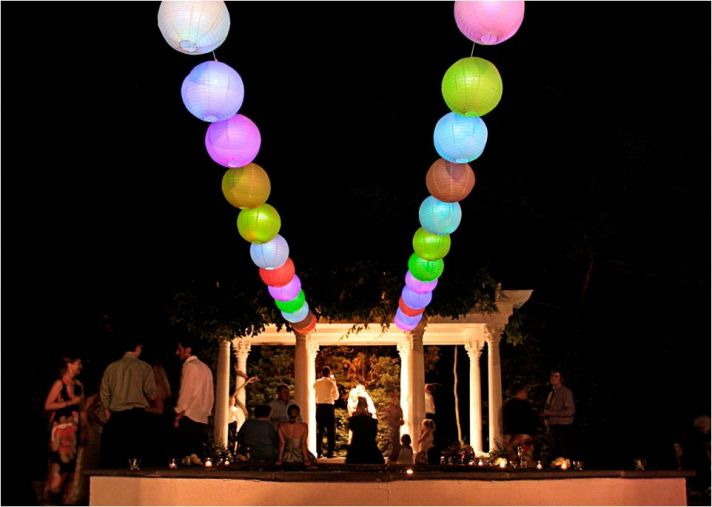 Romantic night outside at wedding ceremony venue- colored lanterns light up the sky