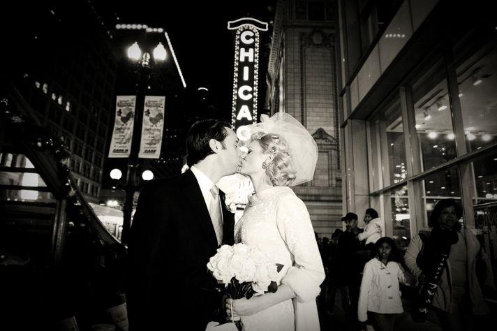 Vintage bride in antique bridal fascinator kisses groom under Chicago theater sign