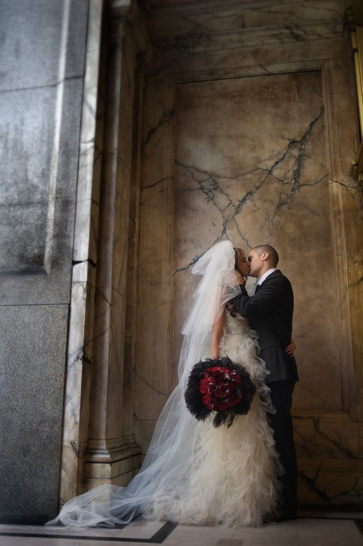 Groom in black tux kisses beautiful bride in strapless ivory beaded and tulle wedding dress