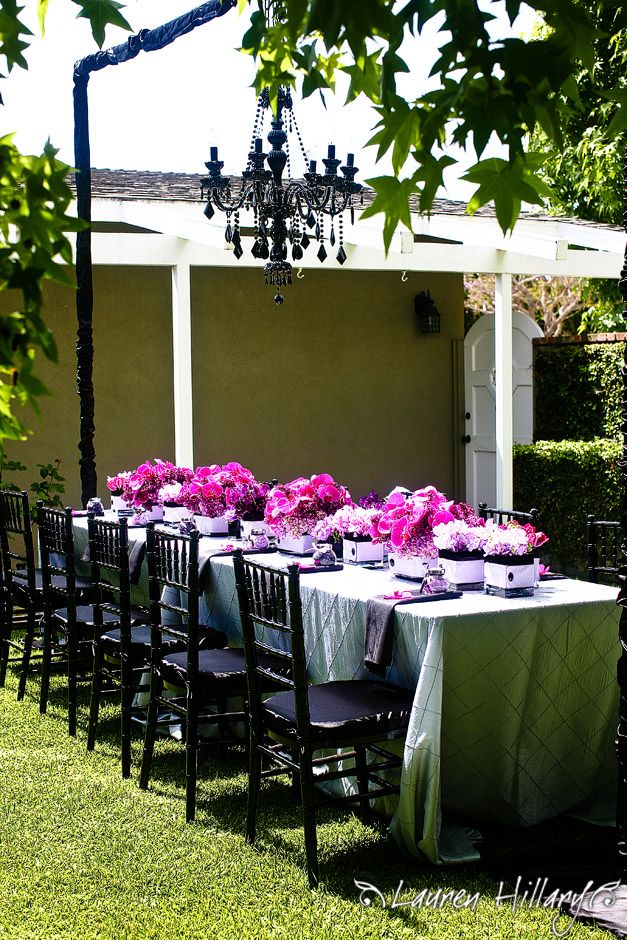 Stunning long bridal shower tablescape with black chairs and chandelier and pink/purple floral arran