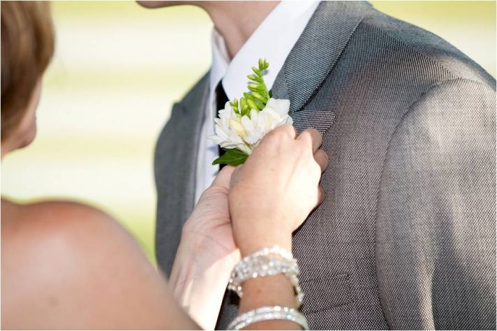Bride pins groom's boutonnière on lapel of casual grey suit