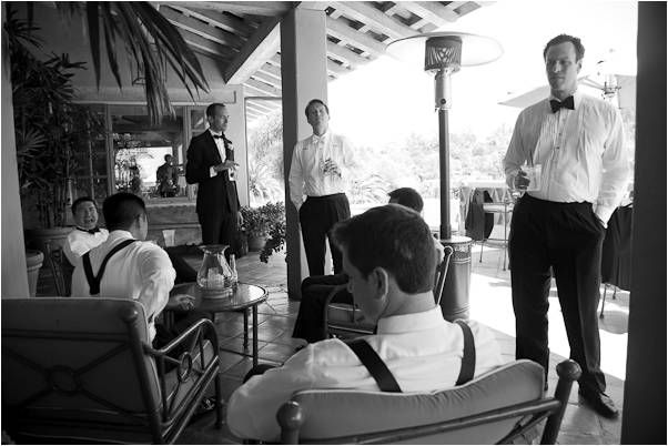 Groom and groomsmen in black tuxedos, black bowtie, white shirt, sip cocktails before wedding ceremo