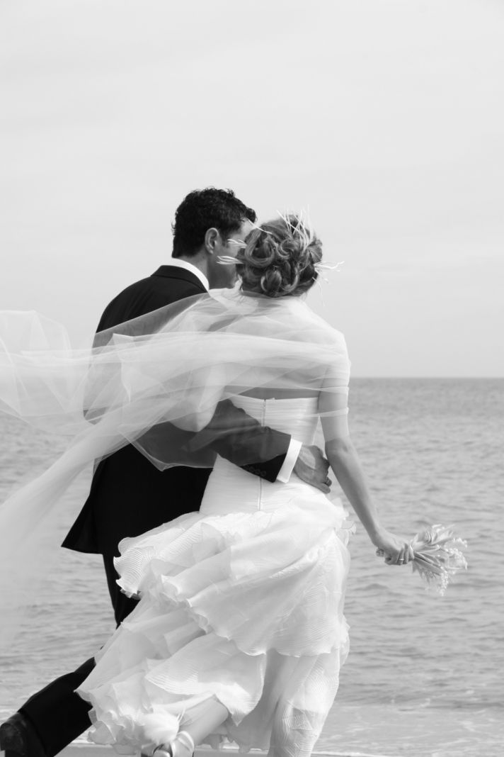 This black and white photo shows a bride and groom walking on the beach after their wedding.