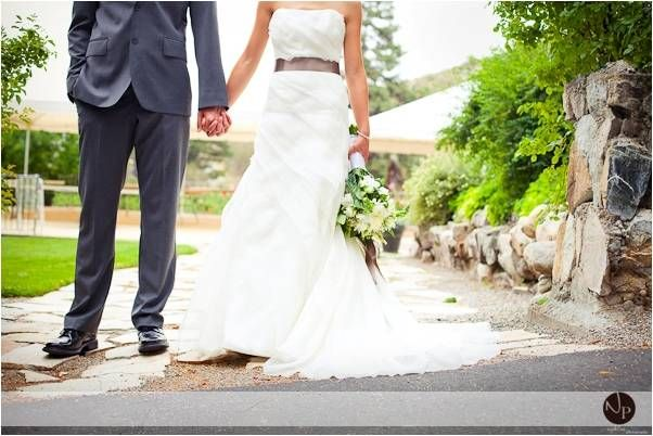 Bride in white wedding dress, taupe ribbon sash, holds hands with her new husband