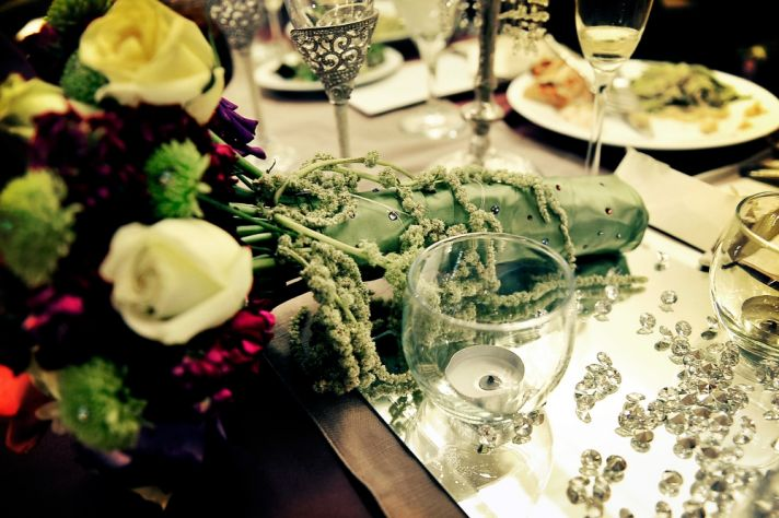 Rich and regal wedding reception decor- ivory, deep purple roses, scattered crystals