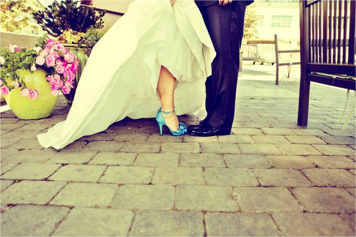 Bride in white sweetheart neckline wedding dress and blue bridal heels poses with groom
