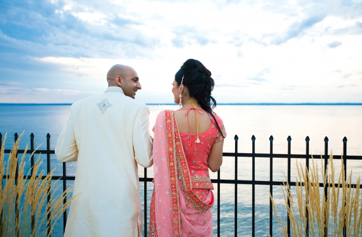 bride-and-groom-stand-outside-waterfront-New-York-reception-venue-pink-red-gold-sari