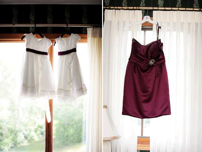 Adorable white flower girl dresses hang in window, with maroon satin bridesmaid dress hanging on the