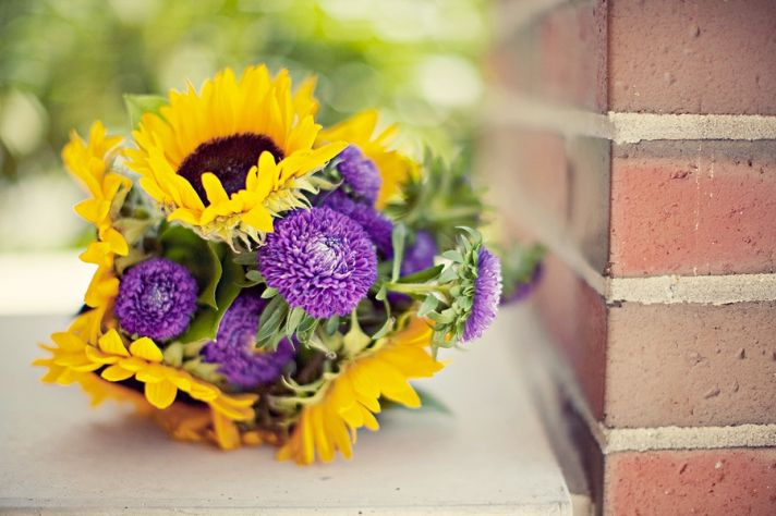 Vibrant bridesmaid bouquet made from sunflowers and purple fresh flowers