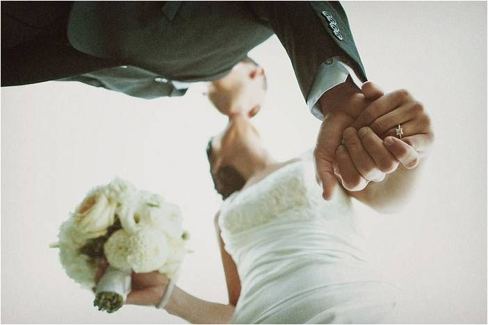 Artistic wedding photo- bride and groom kiss, bride shows off engagement ring