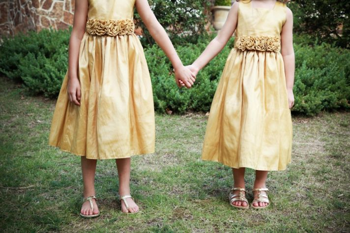 Adorable flower girls in mustard yellow dresses hold hands