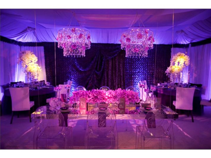 Glammed up wedding reception room with purple lighting and orchids, Ghost chairs and chandeliers