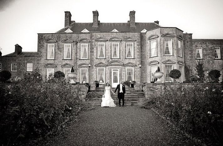 Vintage bride walks down winding staircase of wedding venue to meet her groom