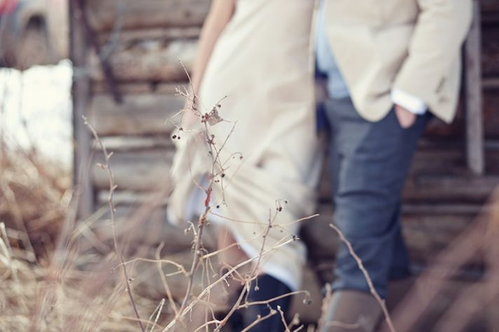 Casual bride and groom take wedding photos outdoors in rustic setting