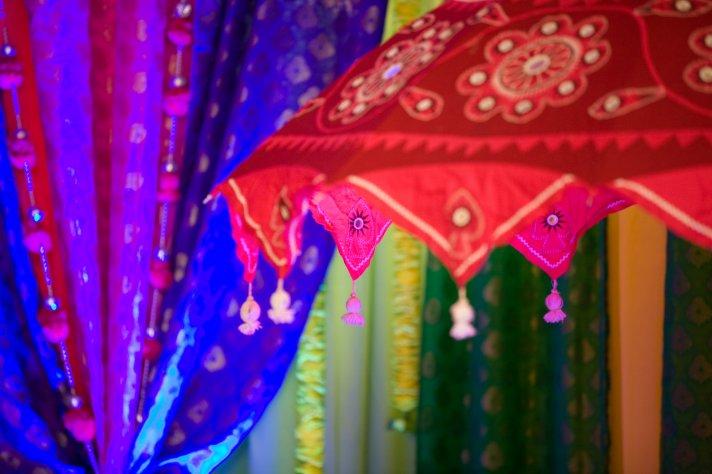 Ornate wedding umbrellas adorn reception room for Indian wedding